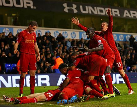 Jon Flanagan of Liverpool is mobbed by his team mates after scoring their third goal during the Barclays Premier League match between Tottenham Hotspur and Liverpool