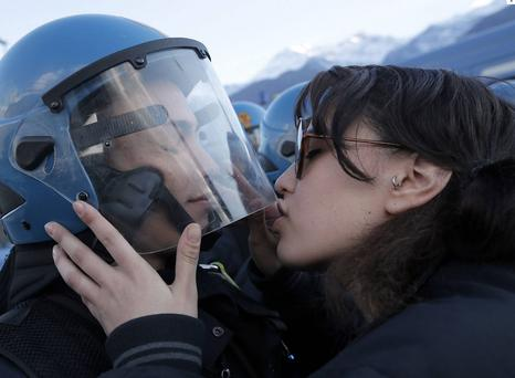 The 20-year-old student was photographed kissing officer Salvatore Piccione during a protest against a planned rail link in Northern Italy. GETTY IMAGES