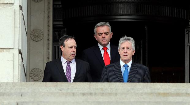 DUP Leader and First Minister Peter Robinson (right) with Nigel Dodds (left) and Johnathan Bell emerge from Stormont to speak to the media, as Robinson has said he would be outraged if proposals for dealing with unresolved issues from the Northern Ireland peace process were not revised.