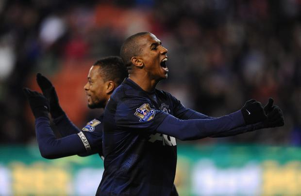 STOKE ON TRENT, ENGLAND - DECEMBER 18: Patrice Evra of Manchester United celebrates scoring his team's second goal with team-mate Ashley Young (r) during the Capital One Cup Quarter Final match between Stoke City and Manchester United at the Britannia Stadium on December 18, 2013 in Stoke on Trent, England. (Photo by Mike Hewitt/Getty Images)