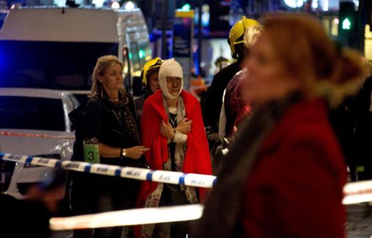 A woman stands bandaged and wearing a blanket given by emergency services following an incident at the Apollo Theatre, in London's Shaftesbury Avenue, Thursday evening, Dec. 19, 2013, during a performance at the height of the Christmas season, with police saying there were