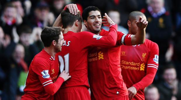 LIVERPOOL, ENGLAND - DECEMBER 21: Luis Suarez (2nd right) of Liverpool celebrates with team mates after scoring during the Barclays Premier League match between Liverpool and Cardiff City at Anfield on December 21, 2013 in Liverpool, England. (Photo by Clive Brunskill/Getty Images)