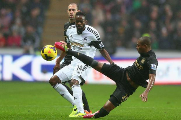 Roland Lamah (L) of Swansea City watches Fernandinho (R) of Manchester City during the Barclays Premier League match