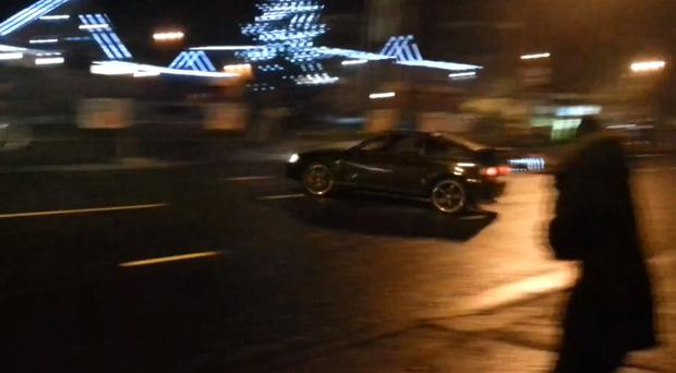 Youths race stolen cars on Belfast's Falls Road, while spectators and police patrols watch, in video footage posted on YouTube .