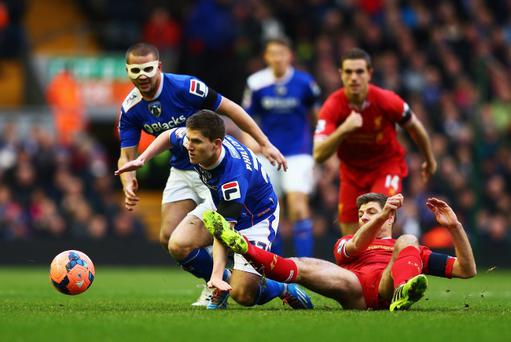 LIVERPOOL, ENGLAND - JANUARY 05: Daniel Philliskirk of Oldham is challenged by Steven Gerrard of Liverpool during the Budweiser FA Cup third round match between Liverpool and Oldham Athletic at Anfield on January 5, 2014 in Liverpool, England. (Photo by Clive Mason/Getty Images)