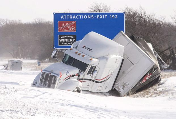 A wrecked semi truck sits in the ditch on the eastbound side of I-74 west of St. Joseph, Ill., on Monday Jan. 6, 2014. Monday morning found east central Illinois encased in bitter cold, sub zero temperatures and blowing snow. (AP Photo/News-Gazette/John Dixon) MANDATORY CREDIT