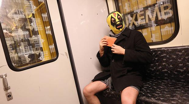 A participant of the No Pants Subway Ride wearing a luchador or Mexican wrestler mask, rides a train on January 12, 2014 in Berlin, Germany.