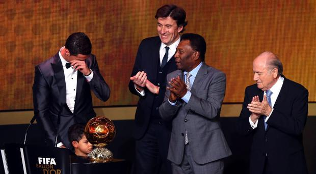 ZURICH, SWITZERLAND - JANUARY 13: FIFA Ballon d'Or winner Cristiano Ronaldo of Portugal and Real Madrid with his son Cristiano Ronaldo Jr accepts his award from FIFA President Joseph S. Blatter and Pele during the FIFA Ballon d'Or Gala 2013 at the Kongresshalle on January 13, 2014 in Zurich, Switzerland. (Photo by Martin Rose/Bongarts/Getty Images)