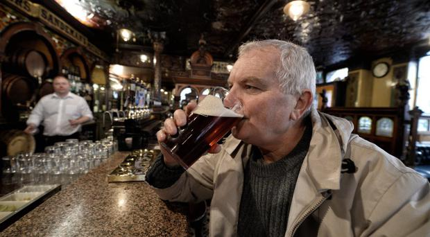 A Crown bar regular tastes his first pint back in the establishment after the recent closure due to an oversight regarding the bars' trading licence renewal. Photo Charles McQuillan/Pacemaker Press