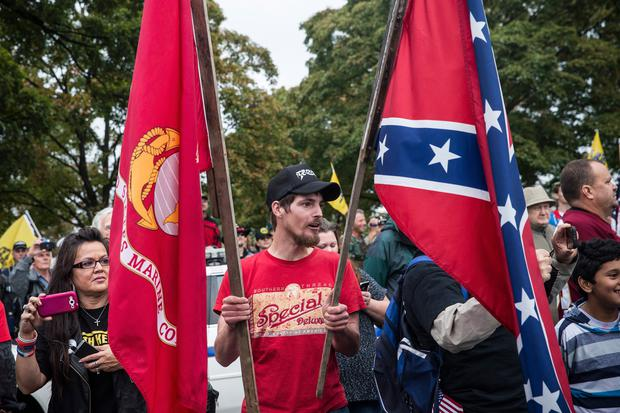 A man carries a Marine flag and a Confederate flag at a rally centered around reopening national memorials closed by the government shutdown, supported by military veterans, Tea Party activists and Republicans, on October 13, 2013 in Washington, DC