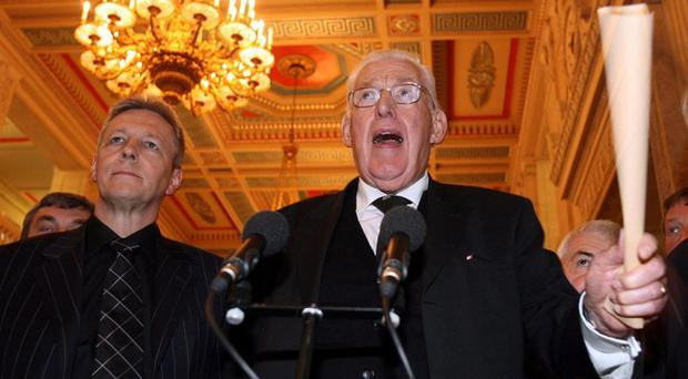 Democratic Unionist Party leader Rev Ian Paisley speaks to the press at Stormont in 2006 while deputy leader Peter Robinson listens.