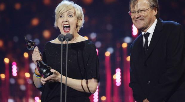 David Neilson (right) congratulates Julie Hesmondhalgh with the award for Serial Drama Performance on stage during the 2014 National Television Awards at the O2 Arena, London