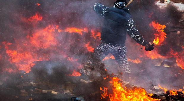 A protester prepares to throw a Molotov cocktail during clashes with police in central Kiev, Ukraine, Wednesday, Jan. 22, 2014. Two people whose dead bodies were found Wednesday near the site of clashes with police have been shot with live ammunition, prosecutors said Wednesday, an announcement that could further fuel violence that spilled on the streets of the Ukrainian capital after two months of largely peaceful protests.(AP Photo/Evgeny Feldman)