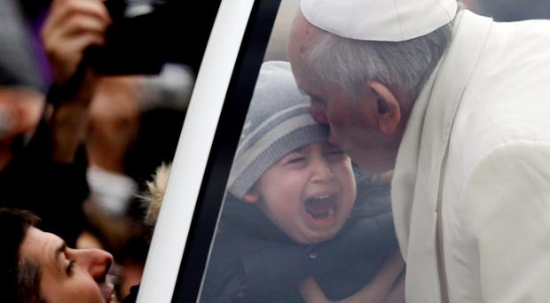 Pope Francis kisses a crying child during his tour through the crowd in St. Peter's Square