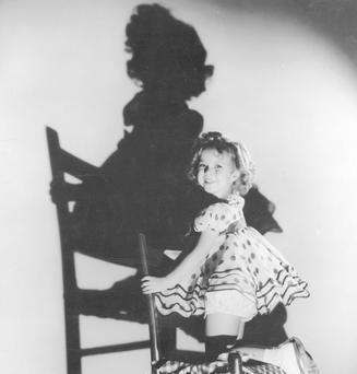 1935: American child star Shirley Temple casts a large shadow on the wall behind her. (Photo by General Photographic Agency/Getty Images)