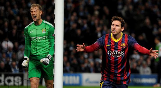 FC Barcelona's Lionel Messi celebrates scoring his teams 1st goal past Manchester City's Joe Hart (left) during the UEFA Champions League, Round of 16 match at the Etihad Stadium, Manchester.