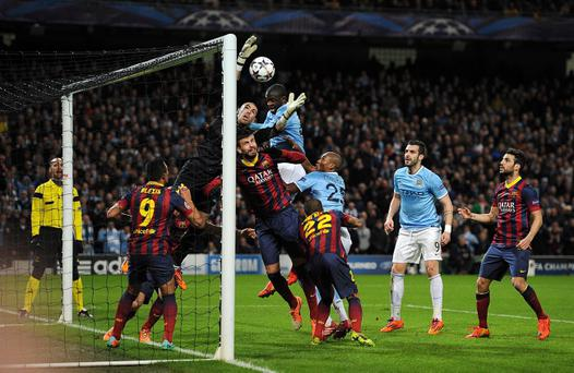 Manchester City's Yaya Toure competes with Barcelona's goalkeeper Victor Valdes for the ball in the air during the UEFA Champions League, Round of 16 match at the Etihad Stadium, Manchester.