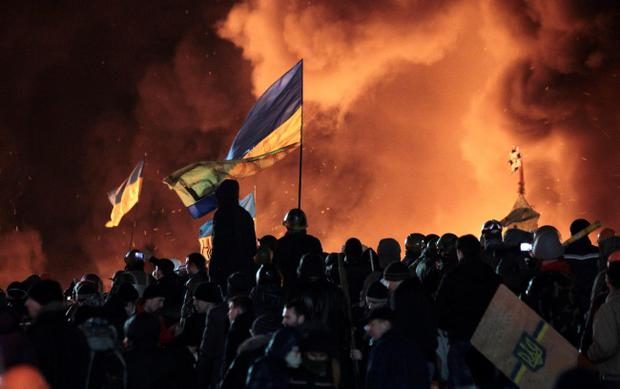 Anti-government protesters clash with riot police in Kiev's Independence Square, the epicenter of the country's current unrest, Kiev, Ukraine, Tuesday, Feb. 18, 2014. Thousands of police armed with stun grenades and water cannons attacked the large opposition camp in Ukraine's capital that has been the center of nearly three months of anti-government protests on Tuesday, after at least nine people were killed in street clashes. (AP Photo/Sergei Chuzavkov)
