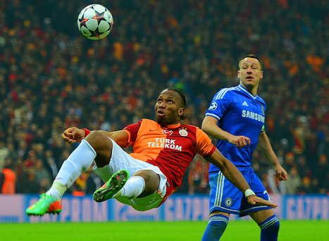 John Terry of Chelsea looks on as Didier Drogba of Galatasaray clears the ball