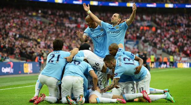 Vincent Kompany and Pablo Zabaleta celebrate the goal scored by Samir Nasri of Manchester City with team mates during the Capital One Cup Final between Manchester City and Sunderland at Wembley Stadium on March 2, 2014 in London, England. (Photo by Jamie McDonald/Getty Images)