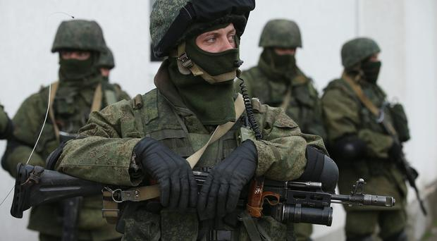 Soldiers who were among several hundred that took up positions around a Ukrainian military base stand near the base's periphery in Crimea on March 2, 2014 in Perevalne, Ukraine. (Photo by Sean Gallup/Getty Images)