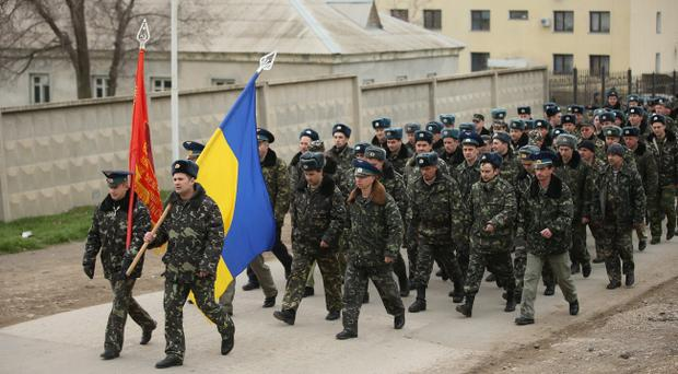 LUBIMOVKA, UKRAINE - MARCH 04: Unarmed Ukrainian troops bearing their regiment and the Ukrainian flags march to confront soldiers under Russian command occupying the Belbek airbase in Crimea on March 4, 2014 in Lubimovka, Ukraine. The Ukrainians are stationed at a garrison nearby, and after spending a tense night anticipating a Russian attack following the expiration of a Russian deadline to surrender, in which family members of troops spent the night at the garrison gate in support of the soldiers, their commander Colonel Yuli Mamchor announced his bold plan this morning to retake the airfield by confronting the Russian-lead soldiers unarmed. The Russian-lead troops fired their weapons into the air but then granted Mamchor the beginning of negotiations with their commander. Russian-lead troops have blockaded a number of Ukrainian military bases across Crimea. (Photo by Sean Gallup/Getty Images)