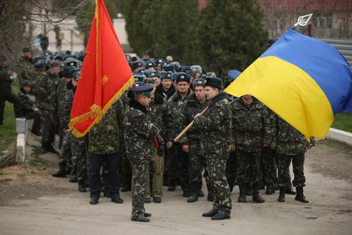 Unarmed Ukrainian troops bearing their regiment and the Ukrainian flags march to confront soldiers under Russian command occupying the Belbek airbase in Crimea on March 4, 2014 in Lubimovka, Ukraine