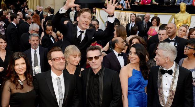 LOS ANGELES, CA - March 02: Actor Benedict Cumberbatch photo bombs the group photo of (L-R) musicians Bono, Larry Mullen, Jr. and Adam Clayton of U2 as they arrive for the Oscars held at Hollywood & Highland Center on March 2, 2014 in Hollywood, California. (Photo by Kevork Djansezian/Getty Images)