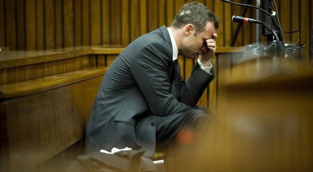 Oscar Pistorius, puts his hand to his head while listening to cross questioning about the events surrounding the shooting death of his girlfriend Reeva Steenkamp, during his trial in Pretoria, South Africa, Friday, March 7, 2014. Pistorius is charged with murder for the shooting death of Steenkamp, on Valentines Day in 2013. (AP Photo/Theana Breugem, Pool)