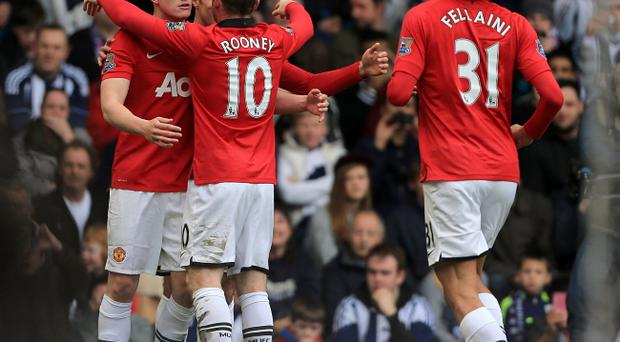Manchester United's Phil Jones (left) celebrates with his team-mate Wayne Rooney (centre) after scoring his team's opening goal during the Barclays Premier League match at The Hawthorns, West Bromwich