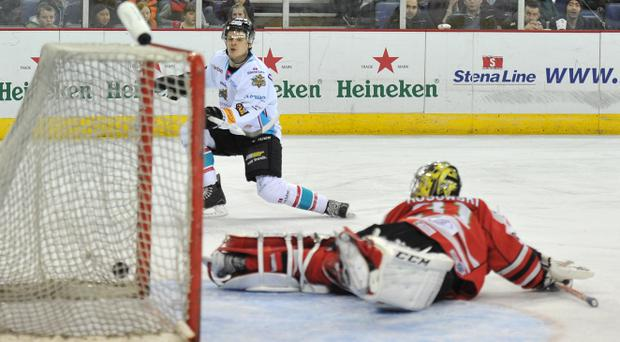 7/3/14: Craig Peacock of the Belfast Giants scores the first goal against the Kamil Kosowski, net minder for the Cardiff Devils during the Elite League game at the Odyssey Arena, Belfast.