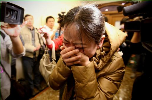 BEIJING, CHINA - MARCH 09: A relative of a passenger onboard Malaysia Airlines flight MH370 cries out at a local hotel where families are gathered on March 9, 2014 in Beijing, China. Malaysia Airline Flight MH370 from Kuala Lumpur to Beijing and carrying 239 onboard was reported missing after the crew failed to check in as scheduled while flying over the sea between Malaysia and Ho Chi Minh City in Vietnam, according to published reports. (Photo by Feng Li/Getty Images) **BESTPIX**