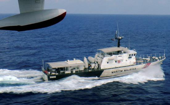 In this photo released by Malaysian Maritime Enforcement Agency, a patrol vessel of Malaysian Maritime Enforcement Agency searches for the missing Malaysia Airlines plane off Tok Bali Beach in Kelantan, Malaysia, Sunday, March 9, 2014. Military radar indicates that the missing Boeing 777 jet may have turned back, Malaysias air force chief said Sunday as scores of ships and aircraft from across Asia resumed a hunt for the plane and its 239 passengers. (AP Photo/Malaysian Maritime Enforcement Agency)