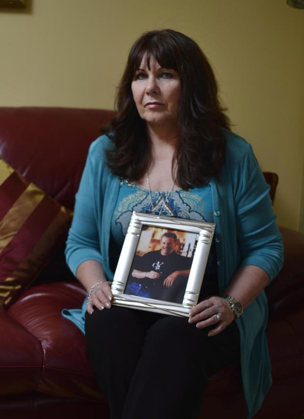 Still missed. Kate Carroll holds a treasured photograph of her murdered husband Stephen. Pic Russell Pritchard / Presseye