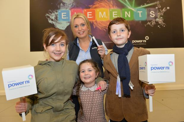 Eimear (age 13), Sean (age 10) and Caoimhe (age 5) O'Keeffe from Belfast join Power NI's Aine Bloomer to help power the launch of the Elements exhibition at the Ulster Museum.