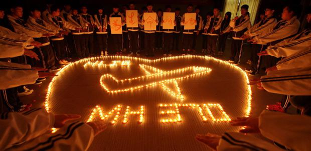 Students from an international school in east China city Zhuji pray for the passengers onboard Malaysia Airlines flight MH370 by lighting candles on March 10, 2014 in Zhuji, China. (Photo by ChinaFotoPress/ChinaFotoPress via Getty Images)