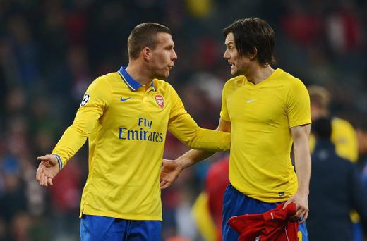 MUNICH, GERMANY - MARCH 11: Lukas Podolski (L) of Arsenal talks to Tomas Rosicky of Arsenal after the UEFA Champions League round of 16, second leg match between Bayern Muenchen and Arsenal at Allianz Arena on March 11, 2014 in Munich, Germany. (Photo by Lars Baron/Bongarts/Getty Images)
