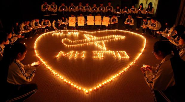 ZHUJI, CHINA - MARCH 10: (CHINA OUT) Students from an international school in east China city Zhuji pray for the passengers onboard Malaysia Airlines flight MH370 by lighting candles on March 10, 2014 in Zhuji, China. (Photo by ChinaFotoPress/ChinaFotoPress via Getty Images)