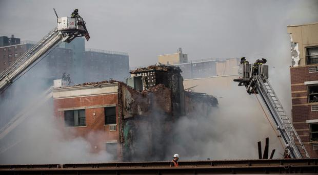 NEW YORK, NY - MARCH 12: Firefighters from the Fire Department of New York (FDNY) respond to a 5-alarm fire and building collapse at 1646 Park Ave in the Harlem neighborhood of Manhattan