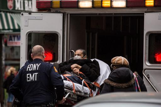 NEW YORK, NY - MARCH 12: Medics put a woman on a stretcher into an ambulance at the scene of a five-alarm fire and building collapse at 1646 Park Ave in the Harlem neighborhood of Manhattan March 12, 2014 in New York City. Reports of an explosion were heard before the collapse of two multiple-dwelling buildings that left at least 17 people injured. (Photo by Andrew Burton/Getty Images)