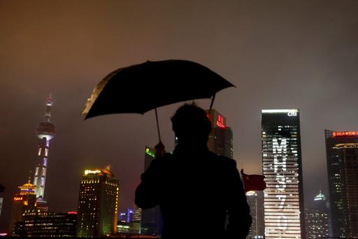 A man stands under an umbrella near an office building with lights forming the words MH370, the flight number of the missing Malaysia Airlines plane in Shanghai