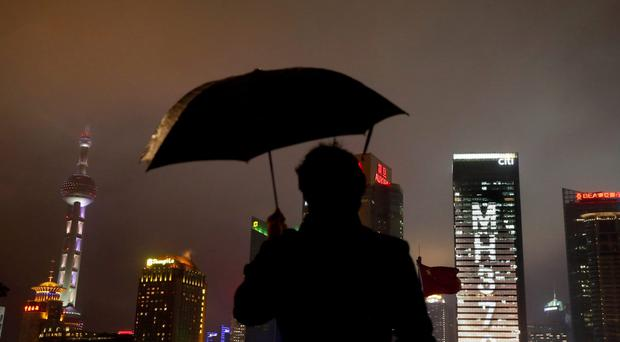 A man stands under an umbrella near an office building with lights forming the words MH370, the flight number of the missing Malaysia Airlines plane in Shanghai (AP)