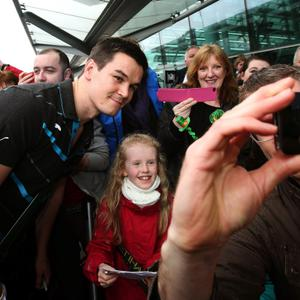 Jonathan Sexton poses with supporters as the Ireland team arrive at Dublin Airport, Ireland.