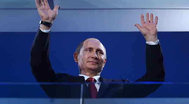 Russia President Vladimir Putin waves during the Sochi 2014 Paralympic Winter Games Closing Ceremony at Fisht Olympic Stadium on March 16, 2014 in Sochi, Russia. (Photo by Dennis Grombkowski/Getty Images)