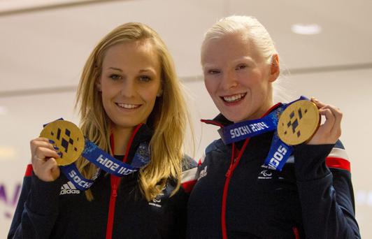Paralympic medal winners Charlotte Evans (left) and Northern Ireland's Kelly Gallagher arrive back at Heathrow Airport, London. Picture date: Monday March 17, 2014. Photo: Steve Parsons/PA