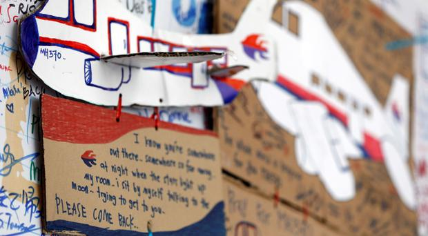 A message card is seen below a paper plane of a Malaysian airliner, on the message board for passengers aboard a missing Malaysia Airlines plane at Kuala Lumpur International Airport in Sepang, Malaysia, Wednesday, March 19, 2014. (AP Photo/Vincent Thian)