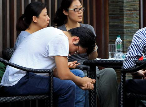 A Chinese relative, in a T-shirt, of passengers aboard a missing Malaysia Airlines plane, looks down as he sits outside a cafe at a resort in Cyberjaya, Malaysia. (AP Photo/Lai Seng Sin)