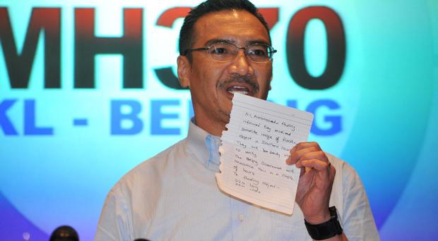 KUALA LUMPUR, MALAYSIA - MARCH 22: Malaysia's Minister of Defence and acting Minister of Transport Hishammuddin Hussein shows a note of latest information from Chinese officials during a press conference on March 22, 2014 in Kuala Lumpur, Malaysia. The press conference was interrupted with breaking news that Chinese satellites had sighted large floating debris in the southern Indian Ocean. (Photo by Rufus Cox/Getty Images)