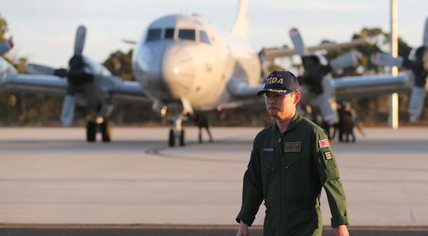 Japanese Commander Hidetsugu Iwamasa walks along the tarmac at Royal Australian Air Force Pearce Base after his P-3C Orion aircraft from Japan Maritime Self-Defense Force arrived to help with search operations for the missing Malaysia Airlines Flight MH370, in Perth, Australia, Sunday, March 23, 2014. (AP Photo/Rob Griffith, Pool)