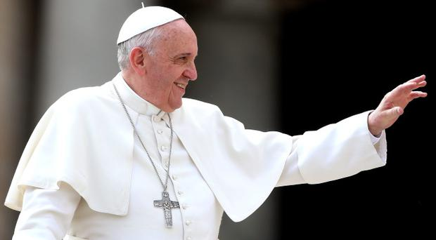 Pope Francis waves to the faithful as he holds his weekly audience in St. Peter's Square